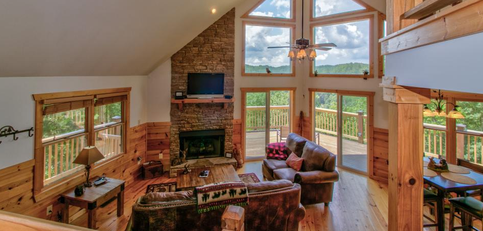 Beautiful cabin interior featuring high ceilings, fireplace, cozy couches and huge windows | Mountain Memories Cabins Georgia